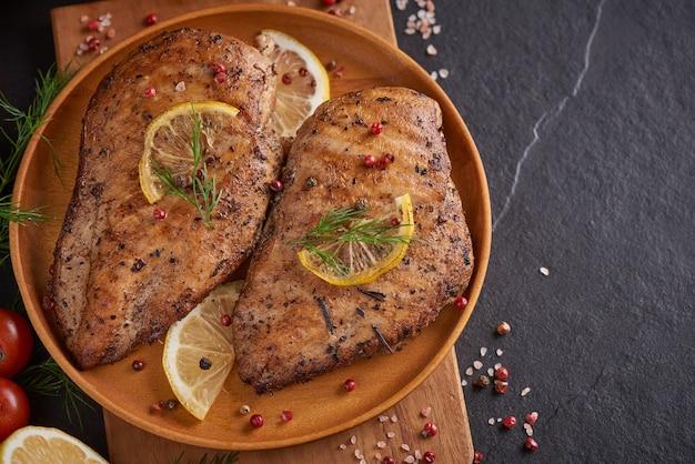 Poitrine de poulet grillée sur une planche de bois et légumes aux tomates et champignons