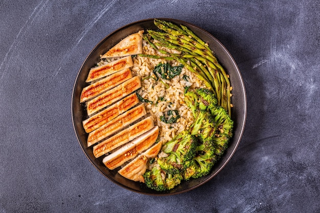 Poitrine de poulet grillée avec riz brun, épinards, brocoli, asperges, concept d'alimentation, alimentation saine.