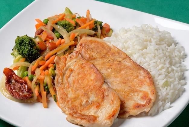 Poitrine de poulet grillée avec riz et salade de légumes.
