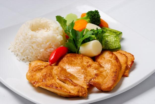 Poitrine de poulet grillée avec riz et salade verte.