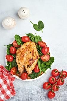 Poitrine de poulet grillée avec salade verte aux épinards, poivrons et tomates cerises dans une assiette en céramique sur fond de tableau blanc. alimentation saine, régime cétogène, concept de déjeuner. vue de dessus et espace de copie