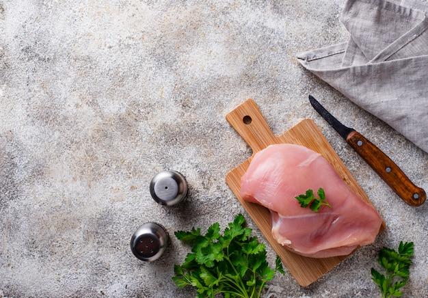 Poitrine de poulet non cuite sur une planche à découper
