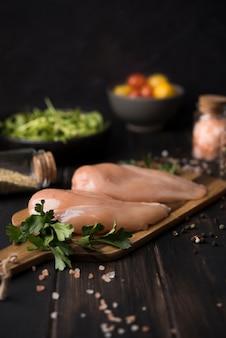Poitrine de poulet sur planche de bois avec des ingrédients