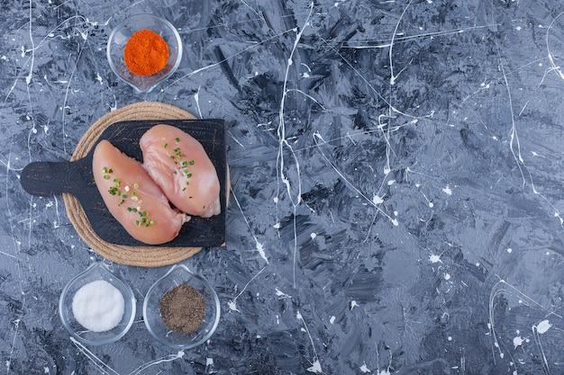 Poitrine de poulet sur une planche à découper sur un dessous de plat à côté de bols pleins d'épices, sur la table bleue.