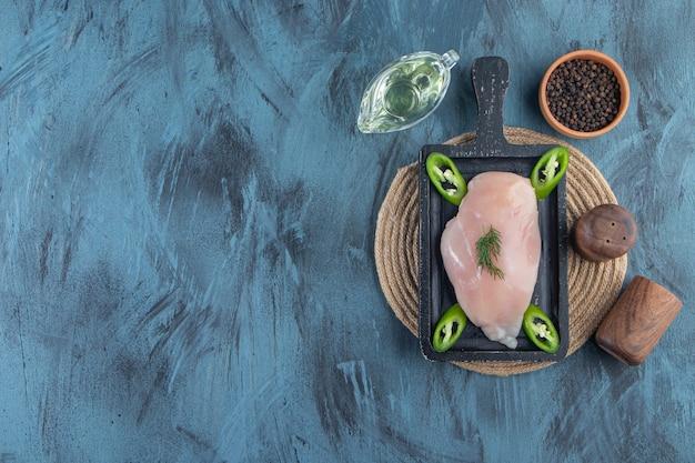 Poitrine de poulet et poivron tranché sur une planche sur un dessous de plat à côté de bols d'épices et d'huile, sur fond bleu.