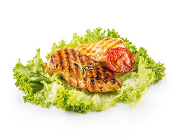 Poitrine de poulet rôtie et grillée avec salade de laitue, tomates et champignons isolés sur blanc