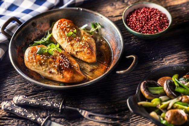 Poitrine de poulet rôtie à l'origan et au poivre dans une poêle avec de jeunes oignons et champignons.