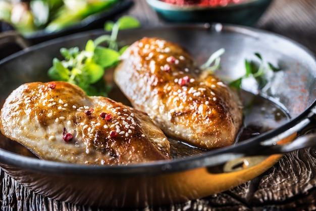 Poitrine de poulet rôtie à l'origan et au poivre dans une poêle.