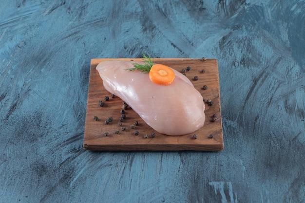 Poitrine de poulet sans peau sur une planche, sur la surface bleue.
