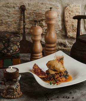 Poitrine de poulet sautée dans un mélange de légumes et de sauce à l'huile.