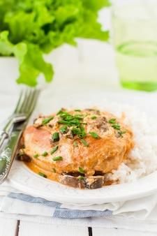 Poitrine de poulet sautée dans une sauce crémeuse aux champignons sur du riz
