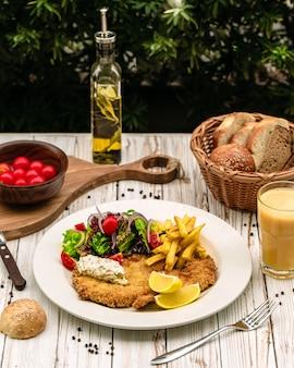 Poitrine de poulet servie avec frites et légumes