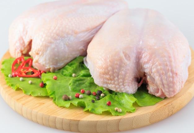 Poitrines de poulet crues sur blanc