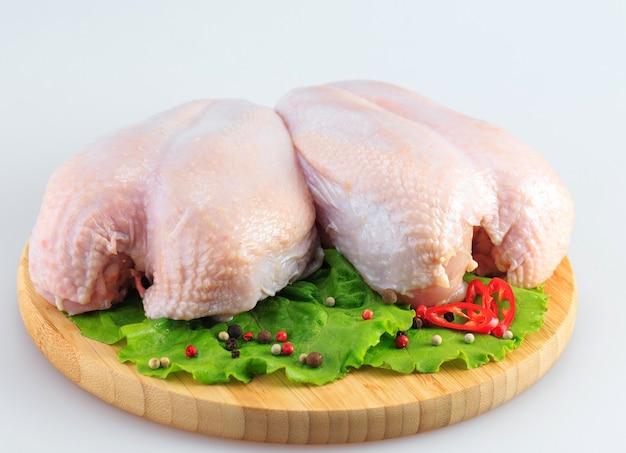 Poitrines de poulet crues sur fond blanc