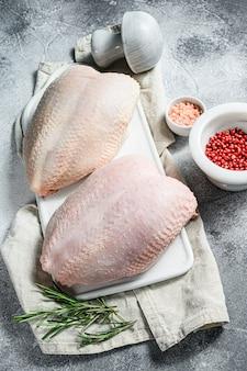 Poitrines de poulet crues sur une planche à découper blanche. oiseau de ferme biologique. filet frais avec peau.