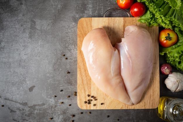Poitrines de poulet crues sur une planche à découper en bois.