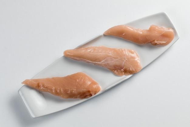 Poitrines de poulet crues sur une plaque blanche moderne