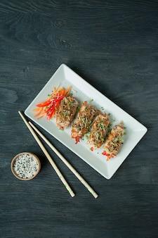 Poitrines de poulet cuites au four aux herbes, tranches de carottes, poivrons sur une planche à découper sombre. style asiatique. l'équilibre d'une alimentation saine. cuisine. fond en bois foncé.