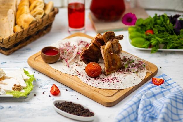 Poitrines de poulet saines marinées, grillées, cuites sur un barbecue estival et servies à la lavash avec des herbes fraîches, du vin, du pain sur une planche de bois, vue rapprochée