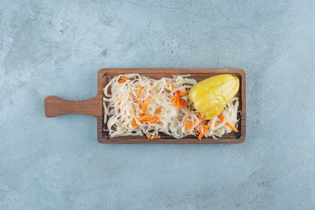 Poivre et choucroute fermentés sur une planche , sur la table bleue.