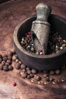 Poivre dans un mortier en bois avec une cuillère