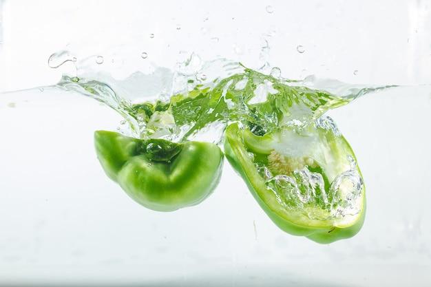 Poivre doux dans les éclaboussures d'eau, poivron vert sur blanc