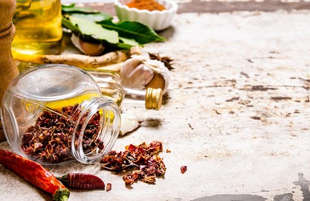 Poivre, feuille de laurier, ail, coriandre en poudre et autres sur table rustique.