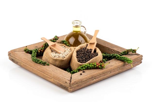 Poivre frais, noir, blanc et huile isolé sur blanc.