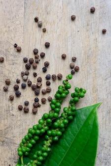 Poivre noir et poivre vert sur fond de bois
