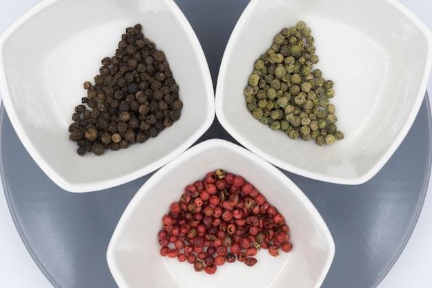 Poivre noir, vert et rouge stockés dans de petits bols carrés
