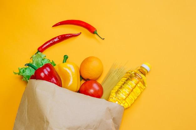 Poivre, piment, huile de tournesol, tomate, orange, pâtes, laitue en emballage artisanal en papier, un ensemble de nourriture végétalienne sur un espace orange