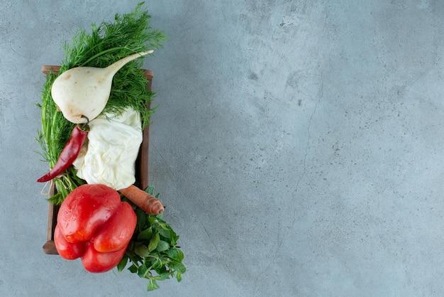 Poivre, radis blanc et légumes verts dans une boîte en bois.