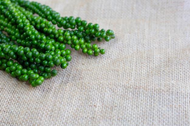 Poivre vert frais sur un sac de toile de fond