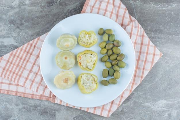 Poivre vert rempli et olive sur plaque blanche.
