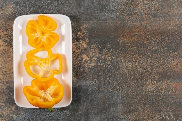 Poivron dans l'assiette sur la surface en marbre