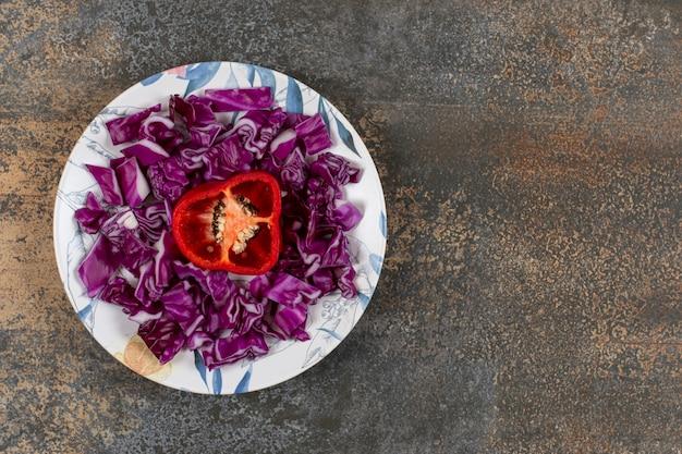Poivron haché dans une assiette de chou rouge finement haché, sur la surface du marbre