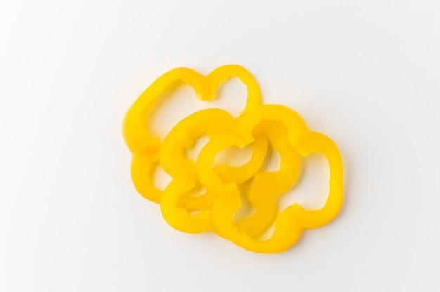 Poivron jaune cru coupé en rondelles sur tableau blanc