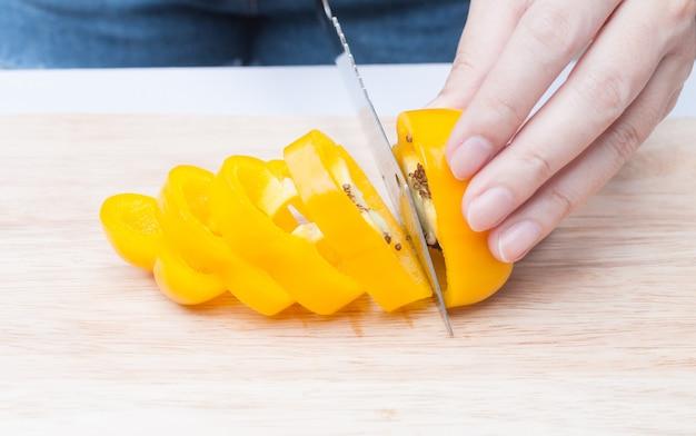 Poivron jaune frais tranché sur planche de bois