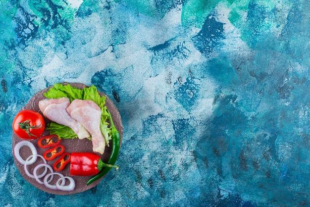 Poivron, rondelles d'oignon, tomate, laitue et pilons de poulet sur une planche, sur le fond bleu.