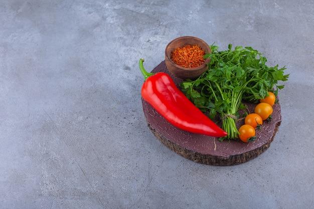 Poivron rouge, feuilles de persil et tomates cerises sur morceau de bois.