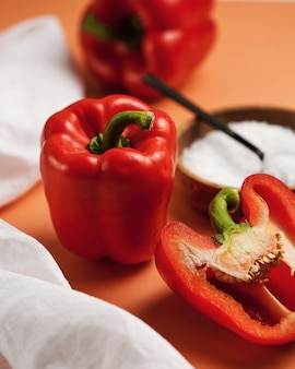 Poivron rouge mûr entier et coupé à côté d'une assiette avec du sel blanc