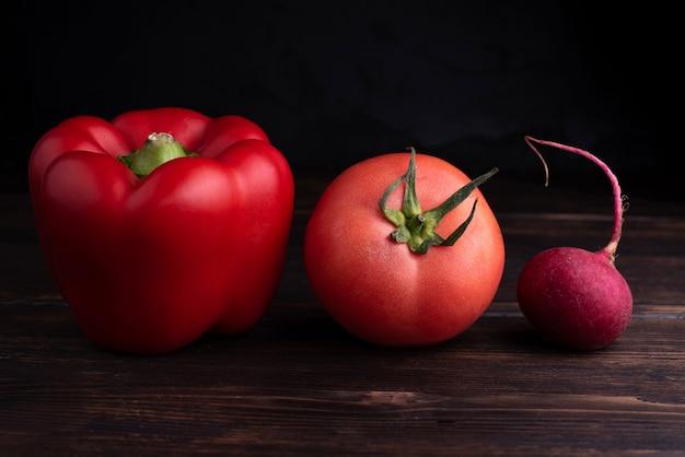 Poivron rouge, tomate, radis rouge sur une table en bois sombre