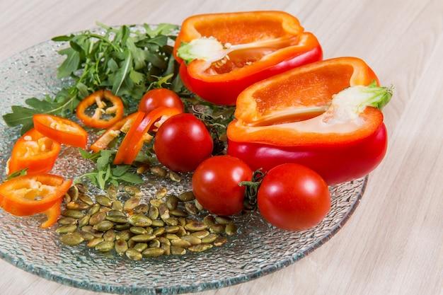 Poivron rouge avec tomates cerise et graines dans une plaque de verre plaque de verre n ingrédients en assiette