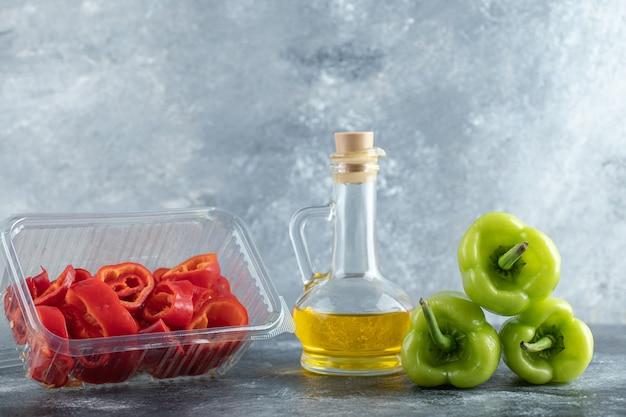 Poivron rouge tranché dans un récipient en plastique avec du poivre vert et une bouteille d'huile sur fond gris