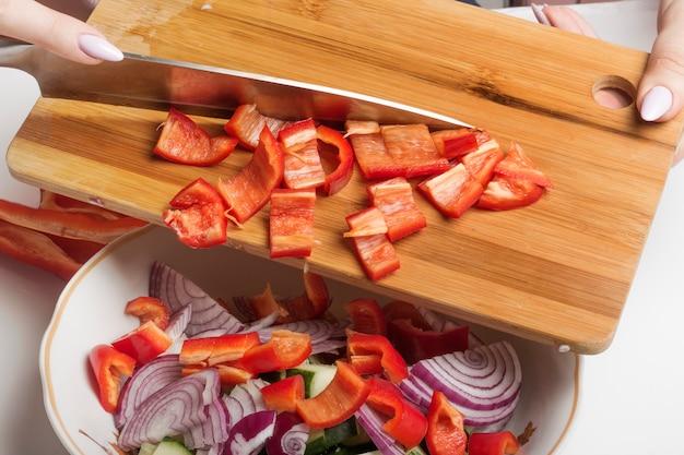 Le poivron rouge tranché sur une planche à découper est transféré dans un saladier.