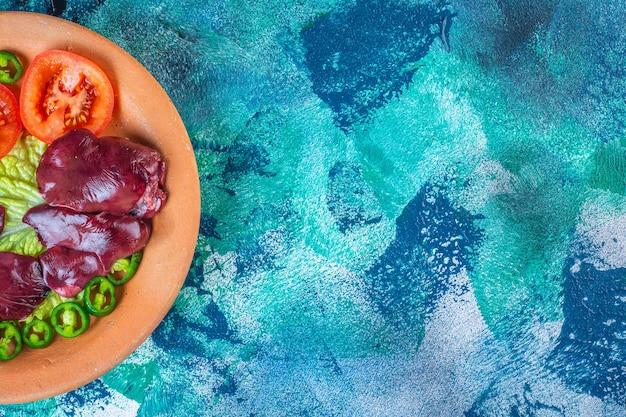 Poivron, tomates, laitue et abats de poulet sur une plaque d'argile