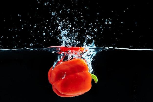 Poivron tombant dans l'eau avec une éclaboussure contre le noir