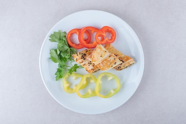 Poivron tranché, persil et crêpes à la viande sur assiette, sur le marbre.