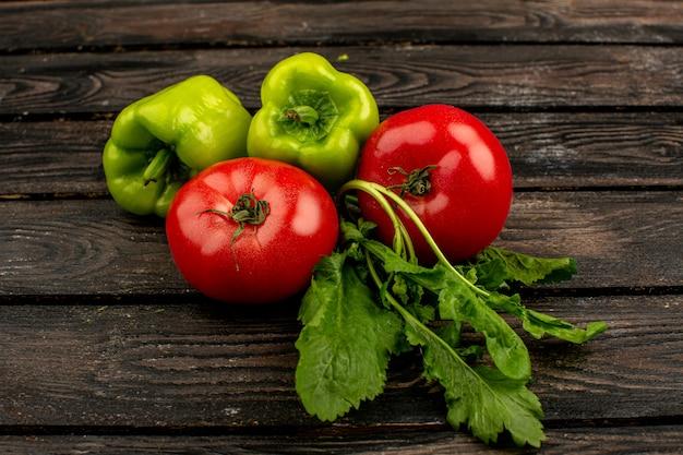 Poivron vert frais mûr avec tomates rouges et verts sur un plancher en bois rustique