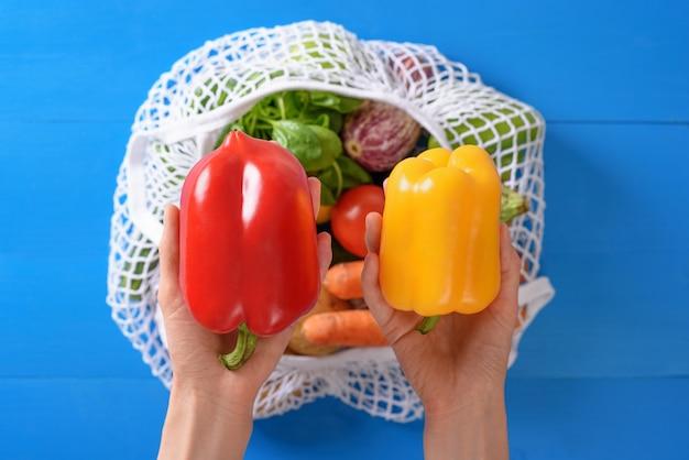 Poivrons, aubergines, épinards, tomates, carottes dans un sac de fil blanc
